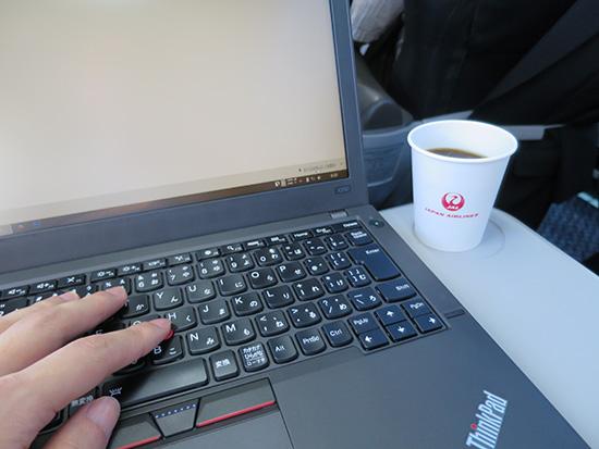 jalのクラスJに搭乗すると飲み物が提供される ThinkPad X250を開きながら